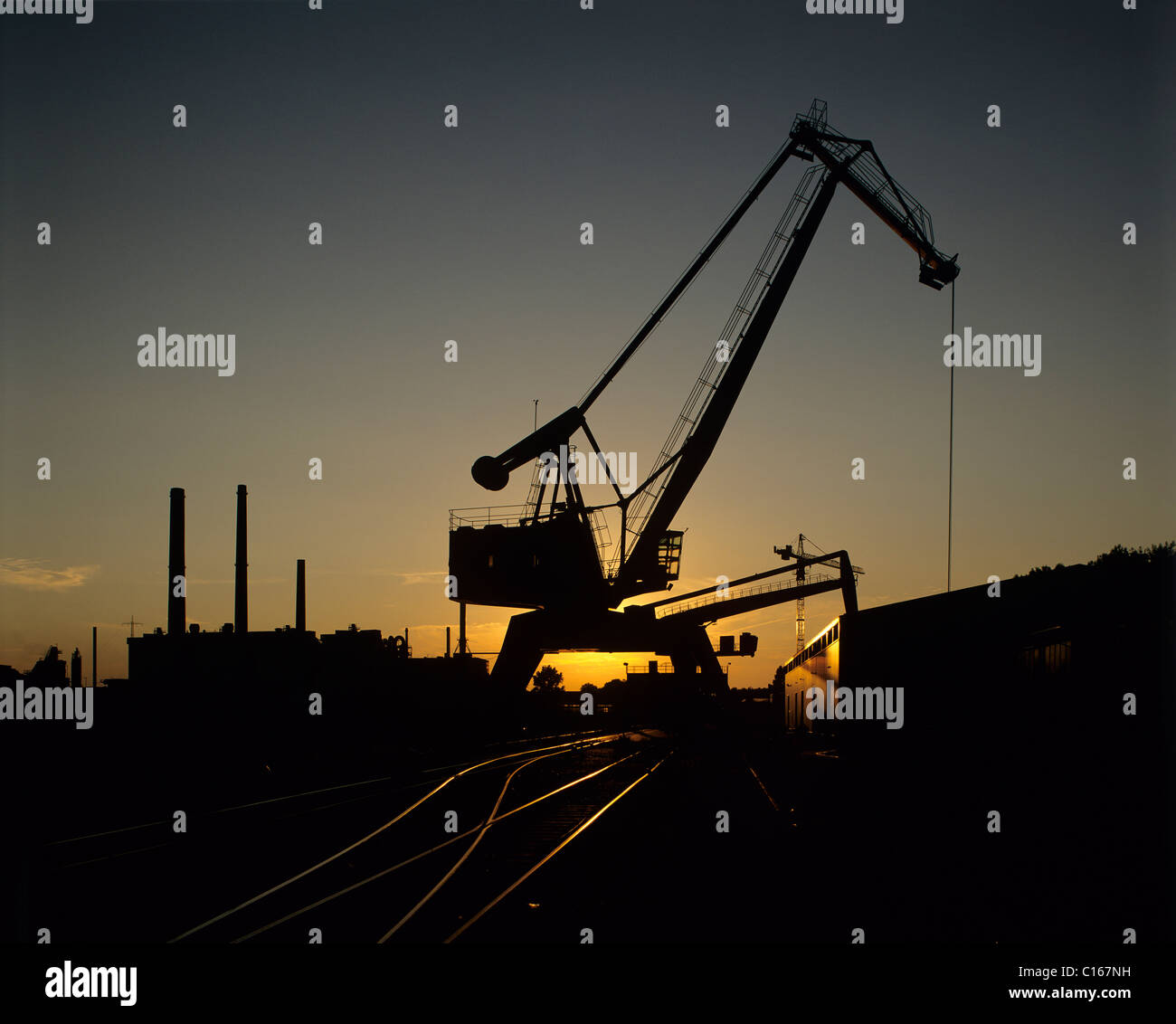 Back lit bulk handling installation, heavy-duty crane and track connection by sunset, silhouette, an industrial - Stock Image