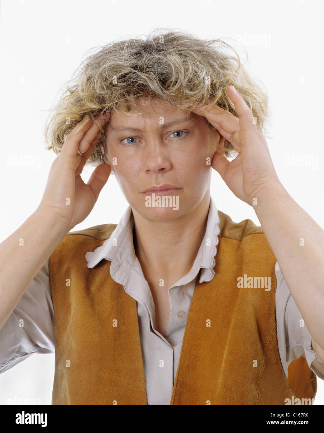 A blond woman is holding her head with both hands, intense headache, migraine, overload - Stock Image