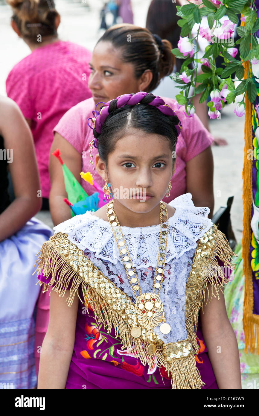 64e0a150c29 proud thoughtful Mexican Indigenous girl costumed for church pageant in  traditional dress with ribbon headdress -