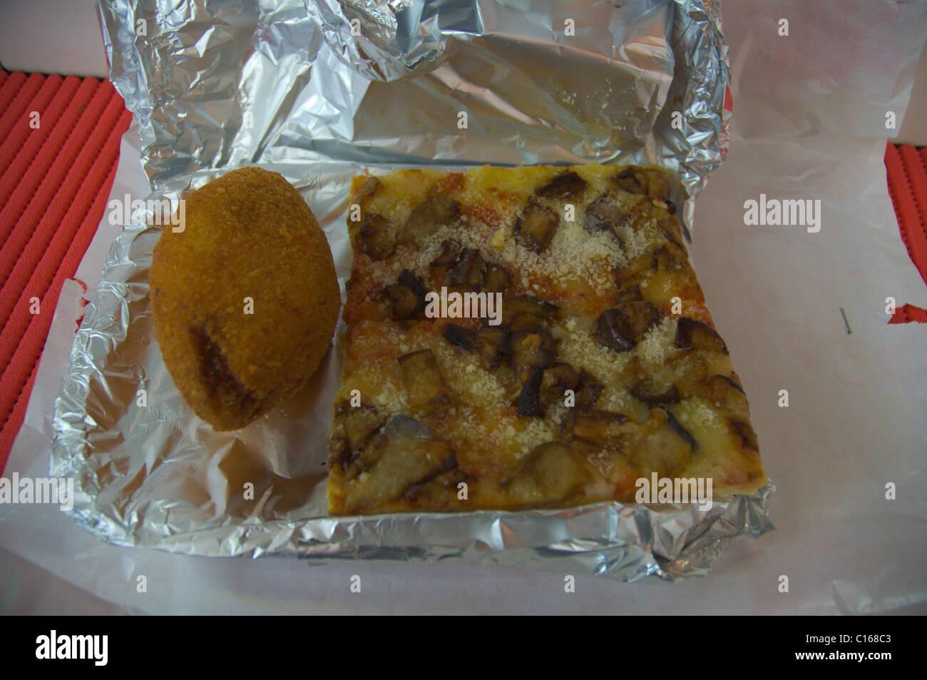 Slice of Sicilian fast foods Pizza alla Norma and Arancino rice ball in Da Christina pizzeria Taormina Sicily Italy Stock Photo