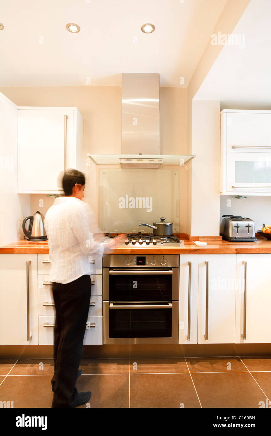 Indian Asian woman in a stylish modern kitchen with white units and a wooden worktop - Stock Image