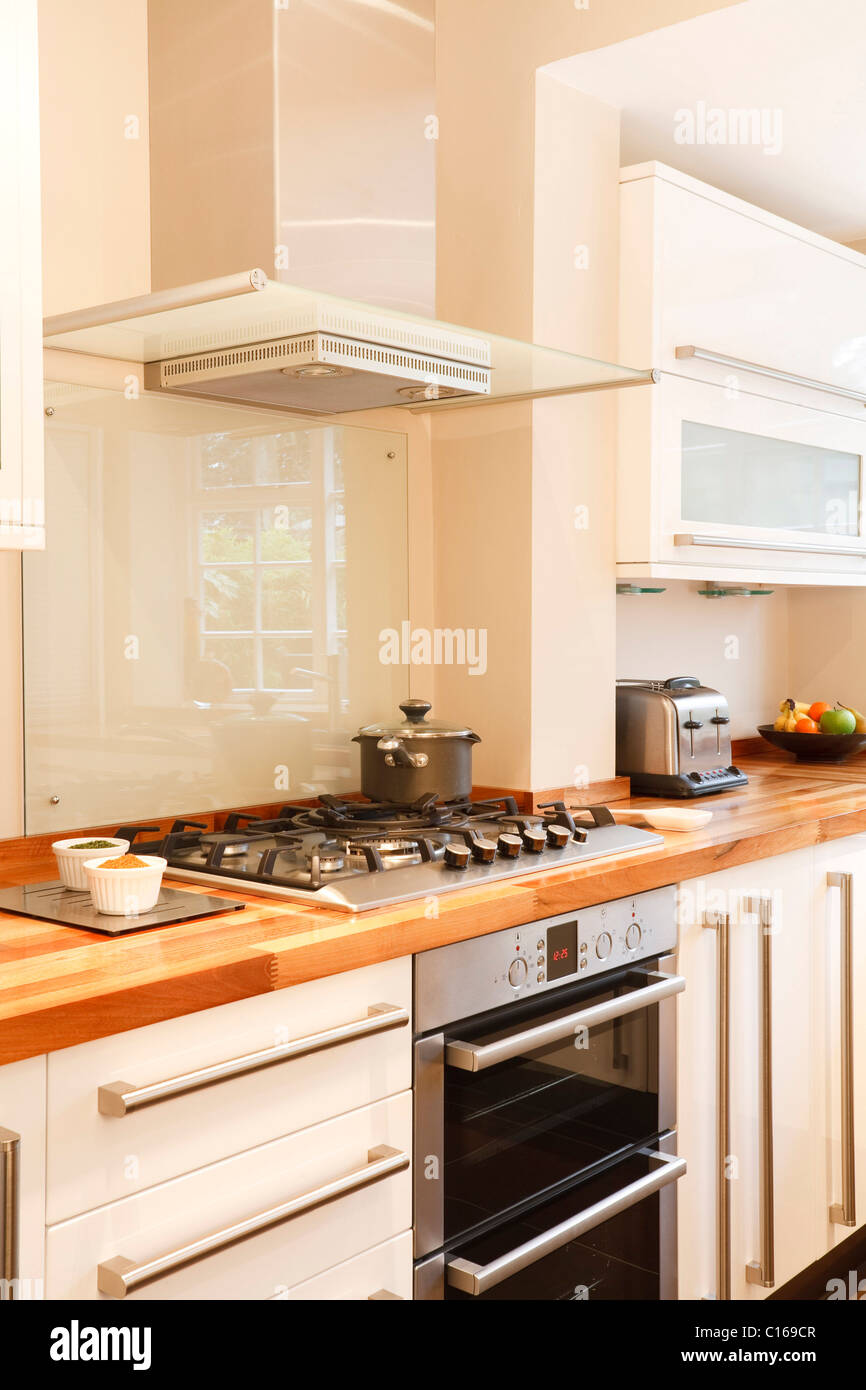 Modern white kitchen with stainless steel cooker, gas hob and chimney extractor - Stock Image
