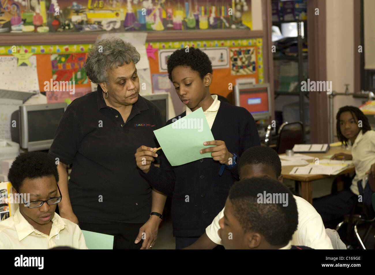 Science teacher works with a student on an assignment at the BRICK Academy Junior High School in Newark, NJ. - Stock Image