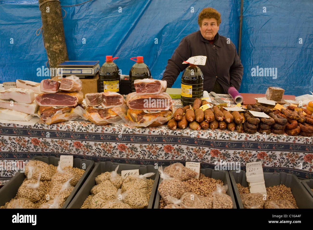 Woman selling meats and beans and cheeses at Saturday morning market in Estremoz, Portugal - Stock Image