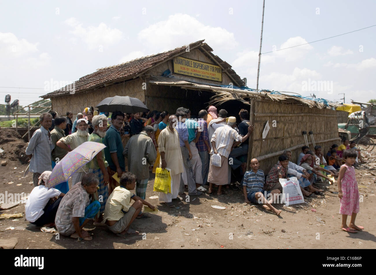 Slum dwellers waiting outside a free outpatient clinic run by the aid organisations Howrah South Point and Aerzte - Stock Image