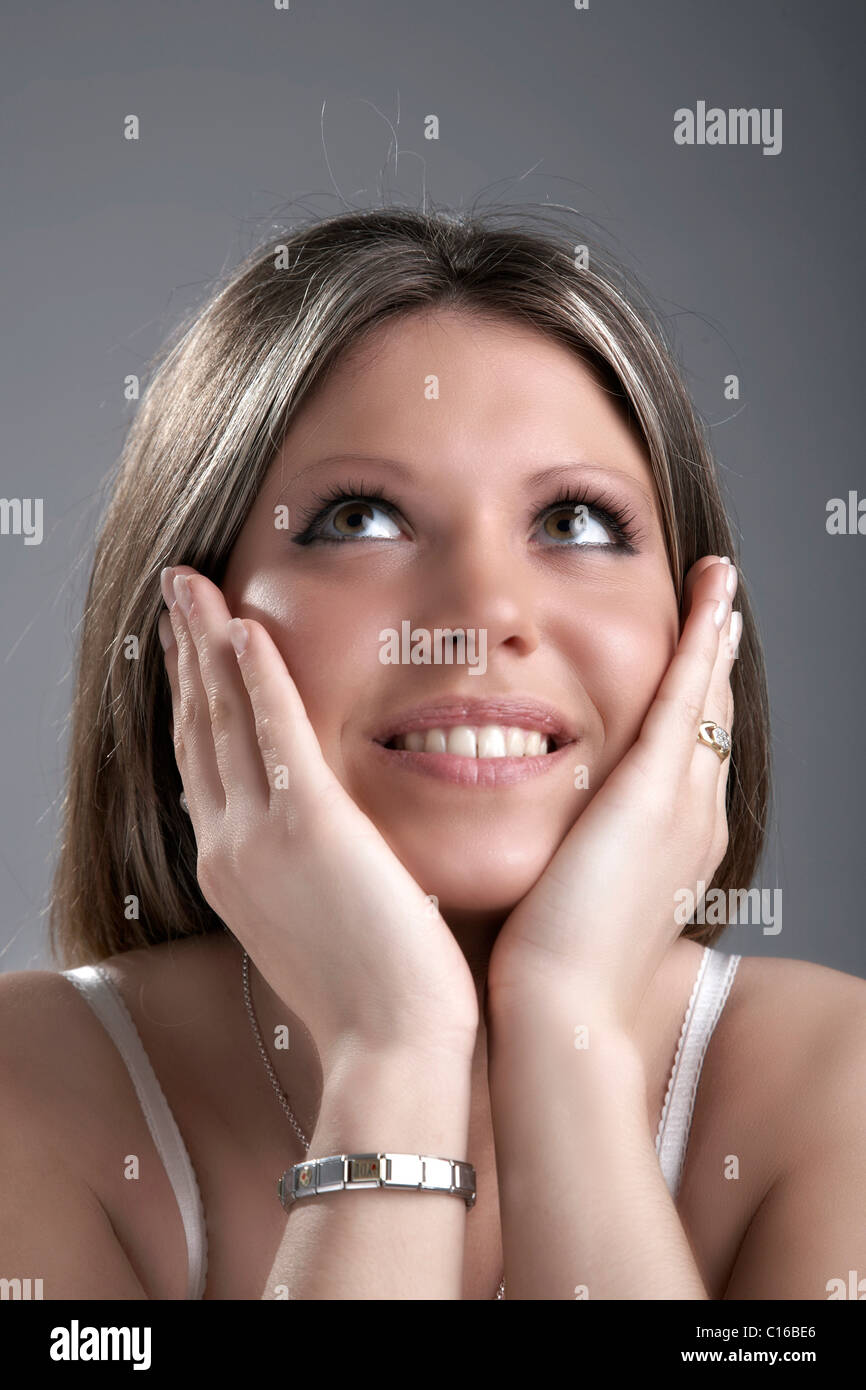 Young woman supporting her head on her hands, looking upwards, entranced - Stock Image