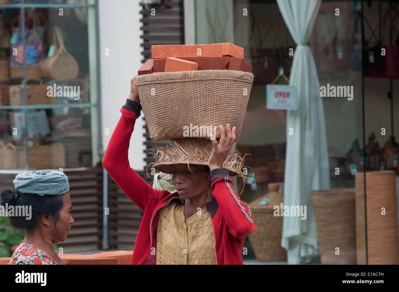 Woman carrying basket of bricks on her head in Ubud Bali - Stock Image