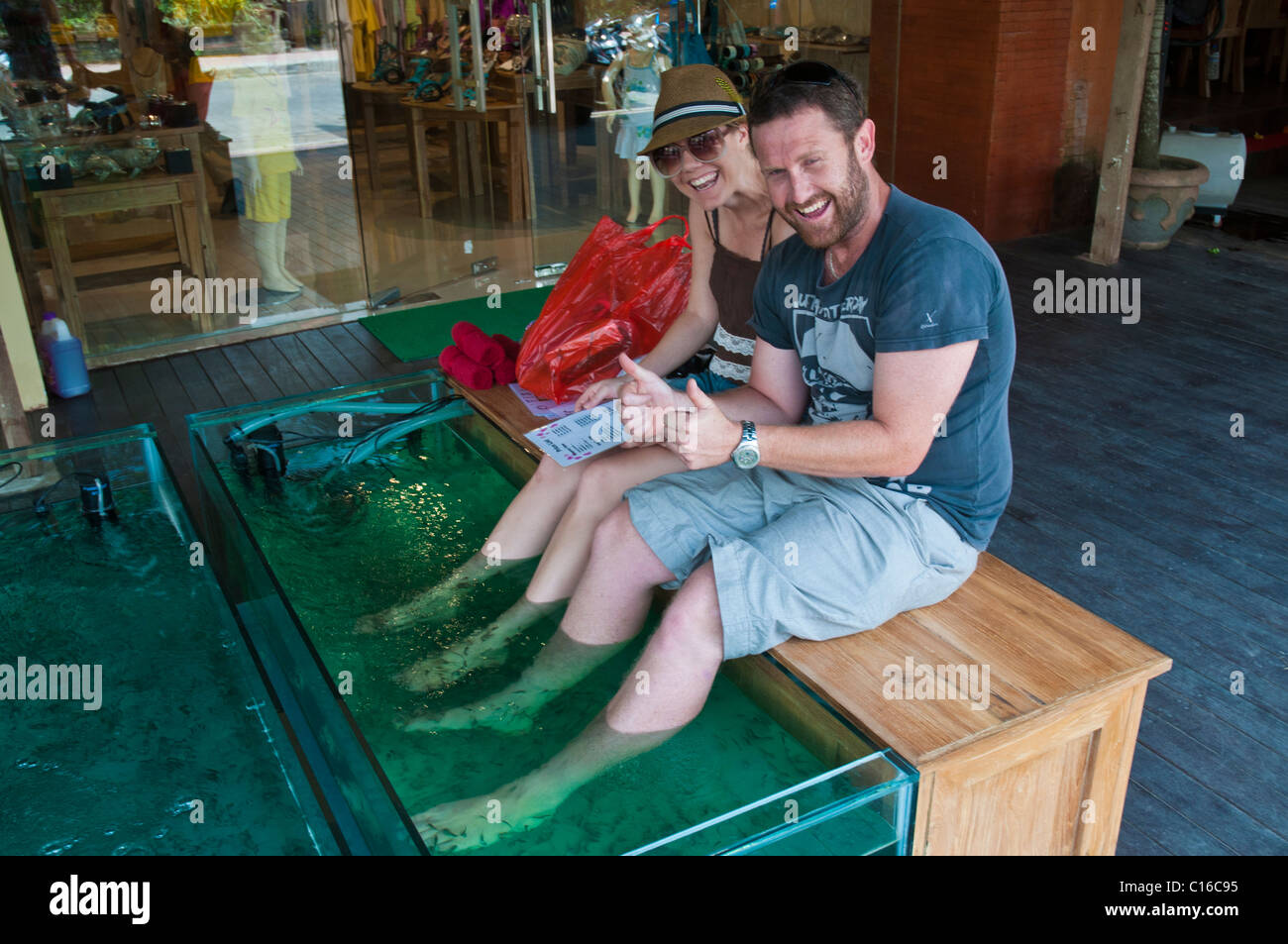Touritst having a fish foot spa in Ubud Bali - Stock Image