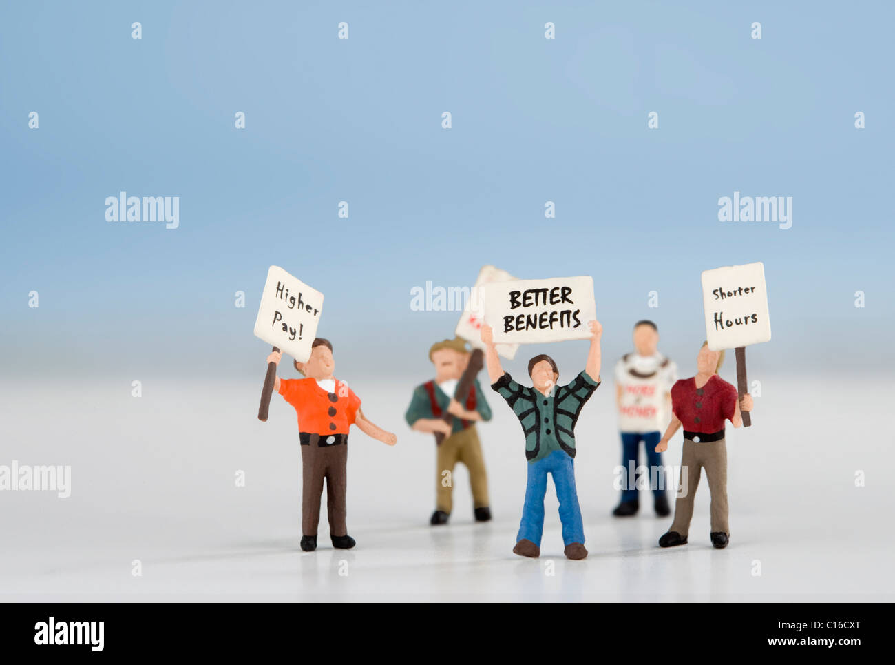 Model figures representing protestors in the street carrying slogans and placards - Stock Image