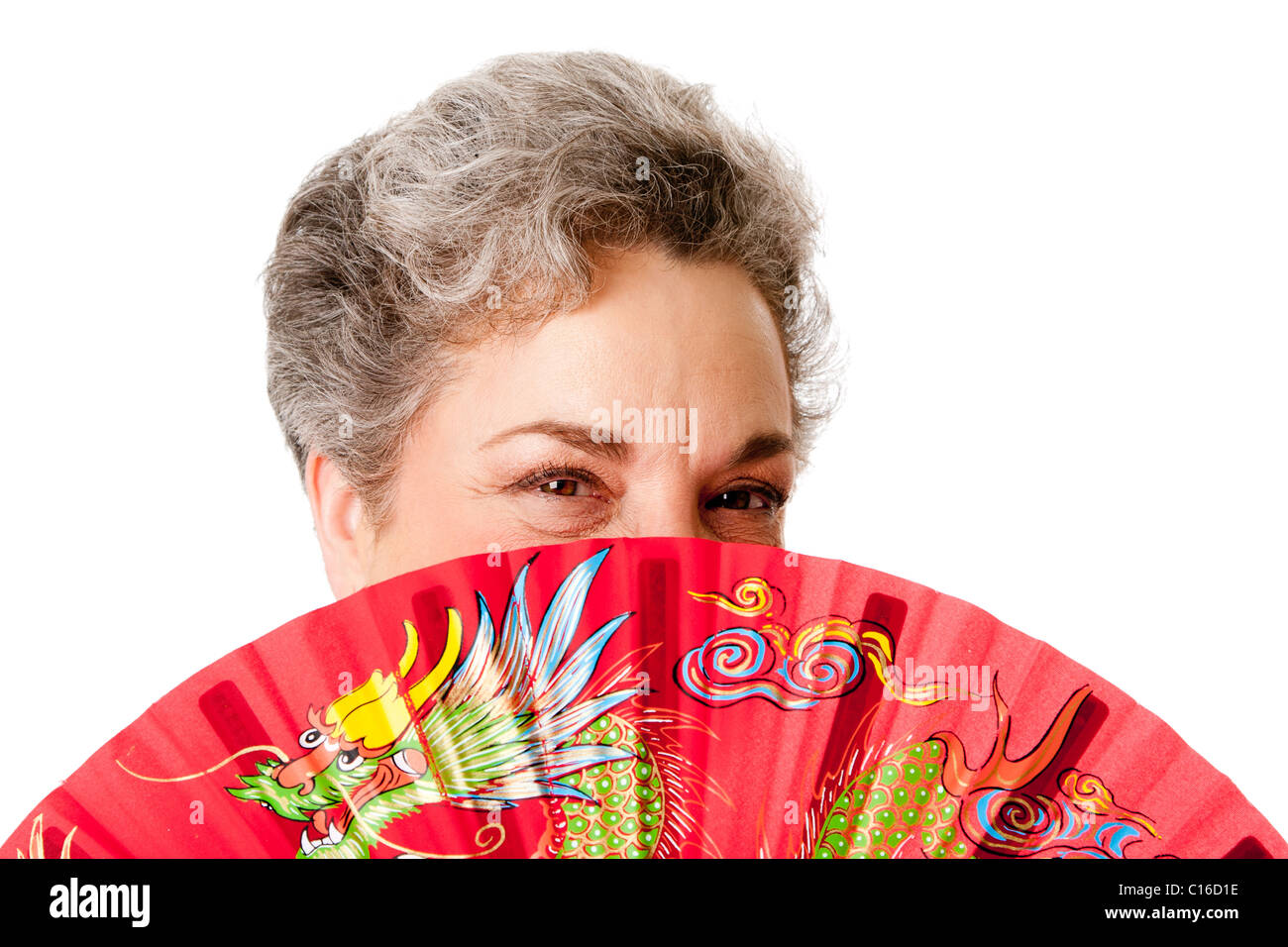 Beautiful Senior woman with gray hair and red Chinese dragon fan, isolated. - Stock Image