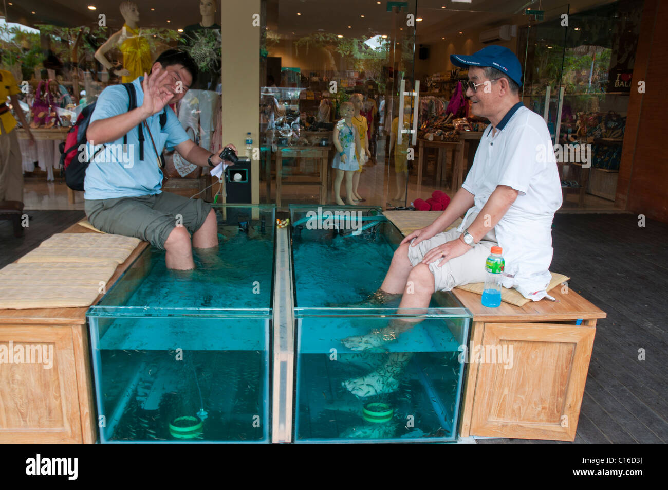 Touritst having a fish foot spa in Ubud Bali - Stock Image