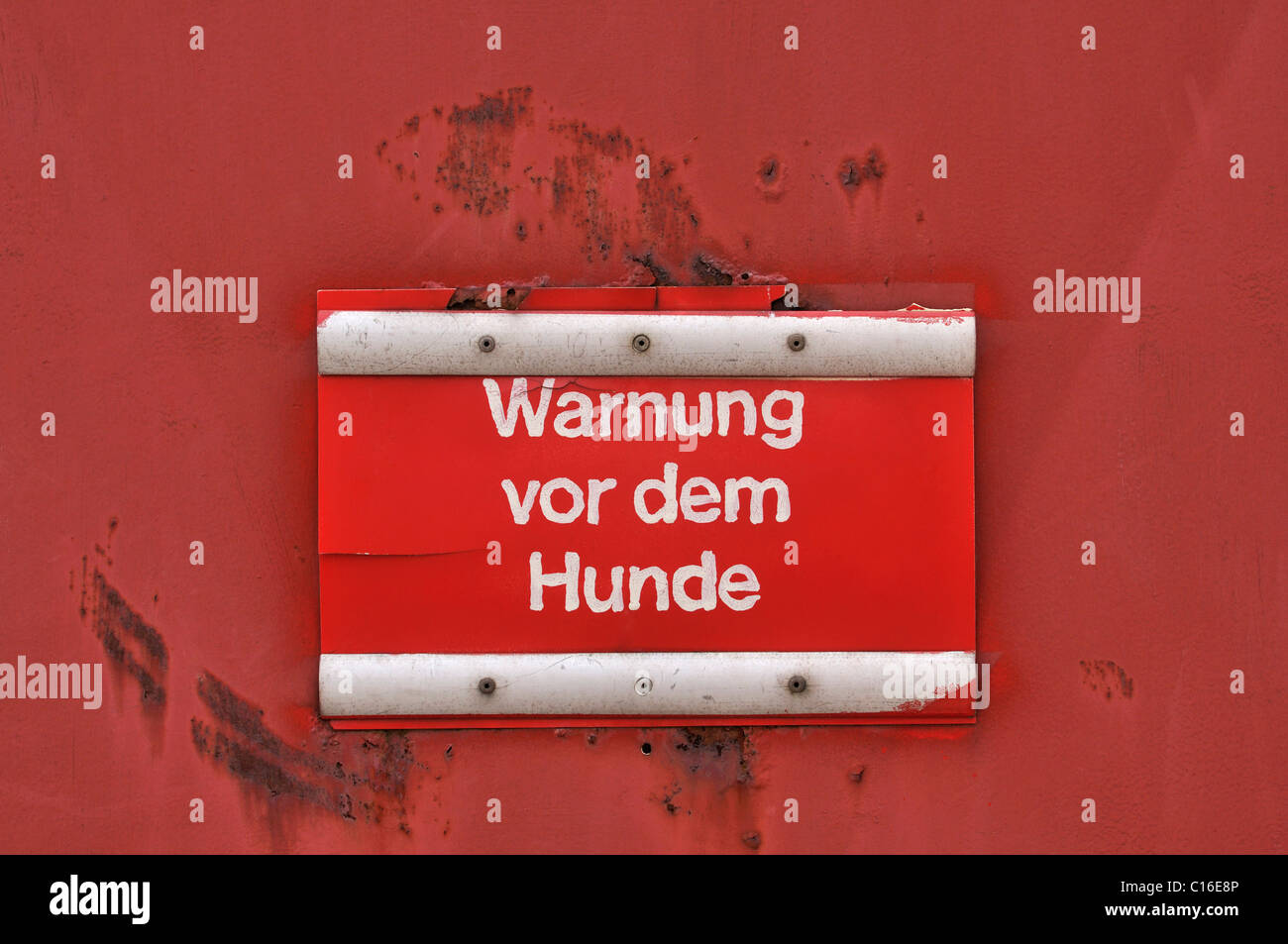 Sign on a rusty red metal door, Beware of the Dog Stock Photo
