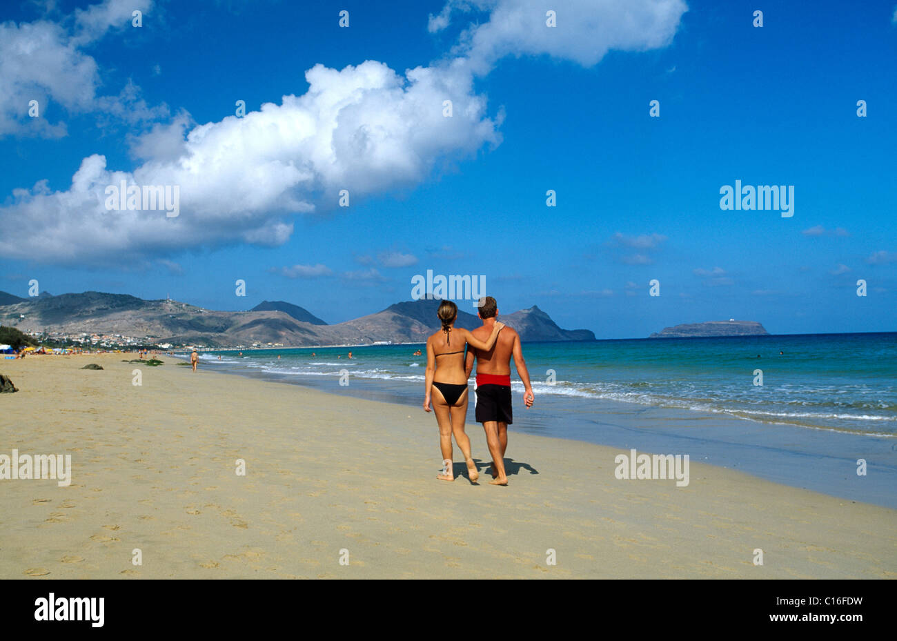 Couple walking along a sandy beach on Porto Santo Island, Madeira, Portugal, Europe - Stock Image