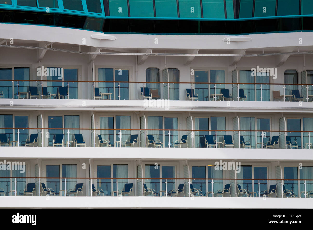 Many deck chairs on rows of balconies outside state rooms of luxury cruise ship - Stock Image