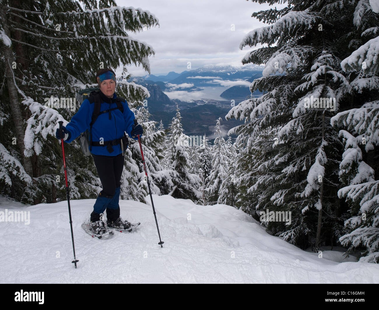Ms snowshoeing relax on th prospect into valley. - Stock Image