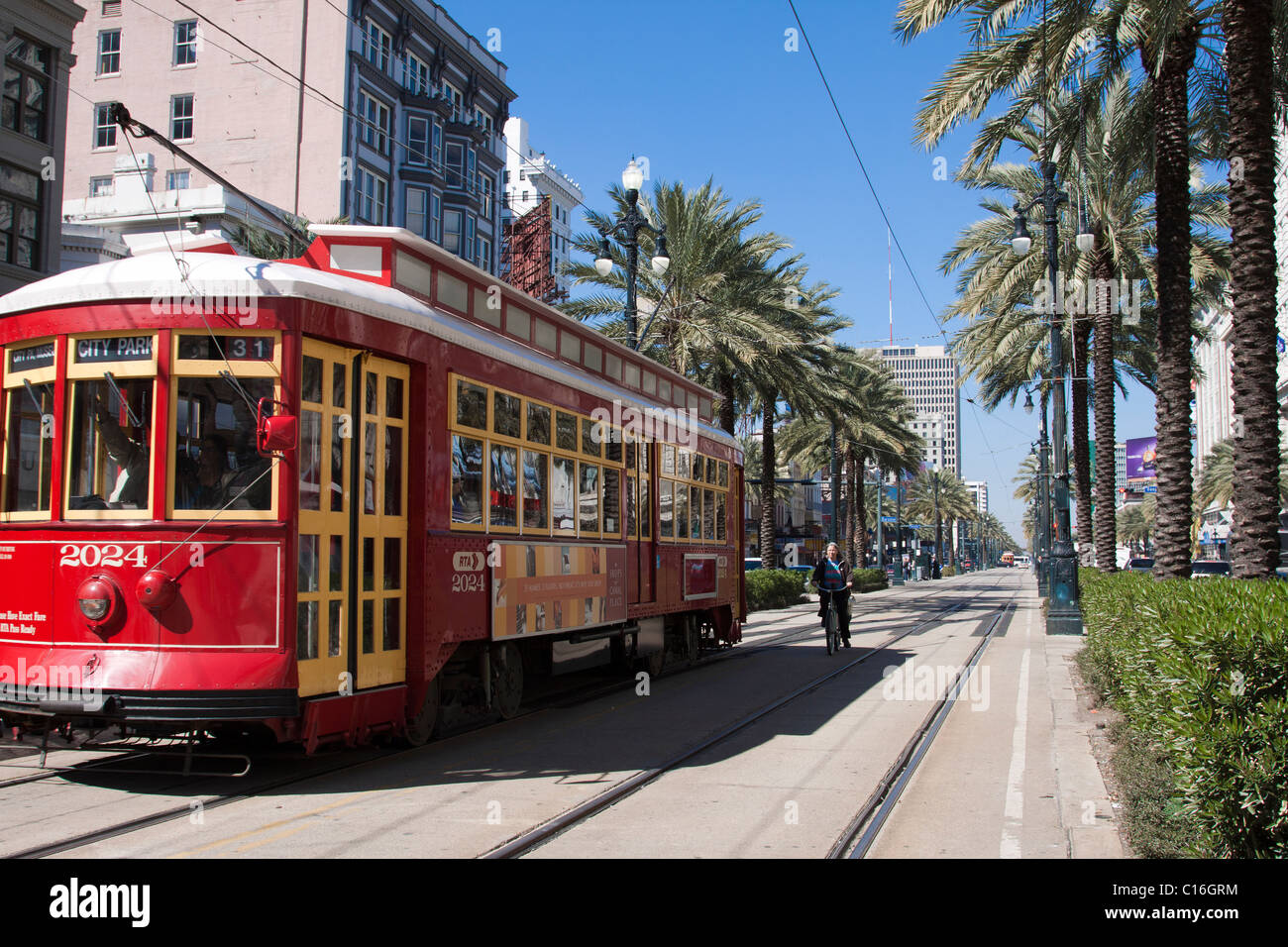 Red trolley car and bicycle on the tracks on Canal Street in downtown New Orleans, Louisiana - Stock Image