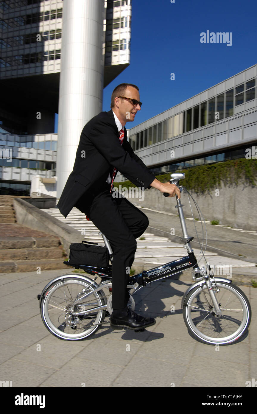 Businessman on his way to work on a folding bike, Hypobank building, Bogenhausen, Munich, Bavaria, Germany, Europe - Stock Image