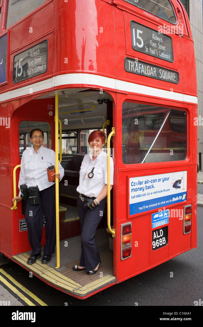 An Asian woman driver and a female conductor on the back of a London red routemaster bus. - Stock Image