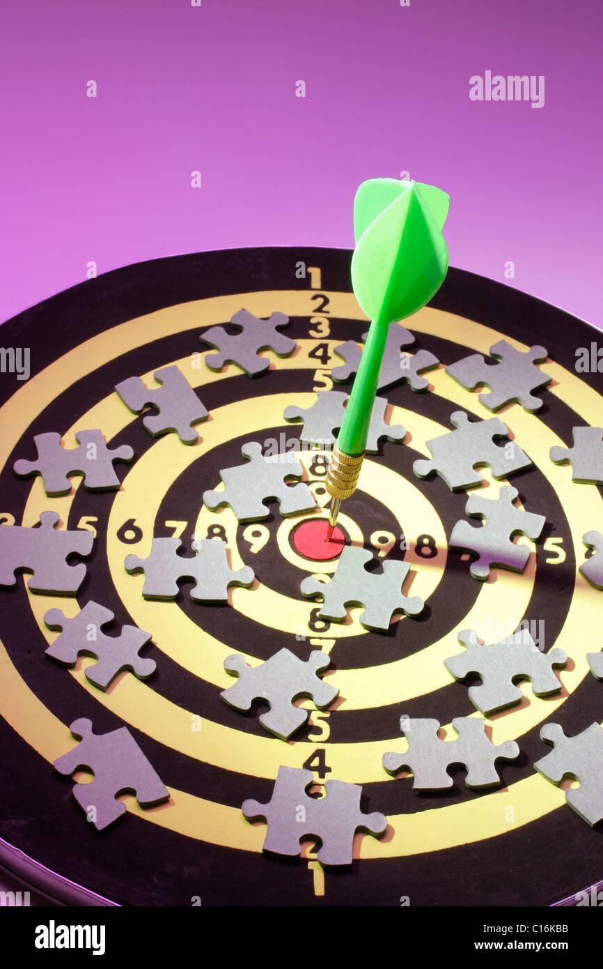 Dart and jigsaw puzzle pieces on dart board - Stock Image