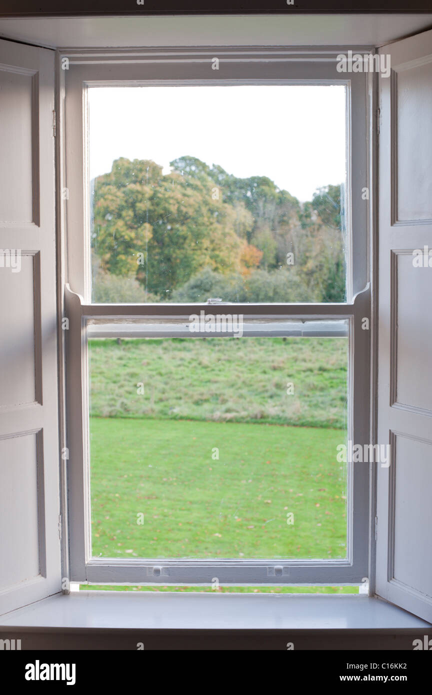 An old farmhouse window with a deep sill looks out onto lawn, field, and woods near Nenagh, Ireland. Stock Photo