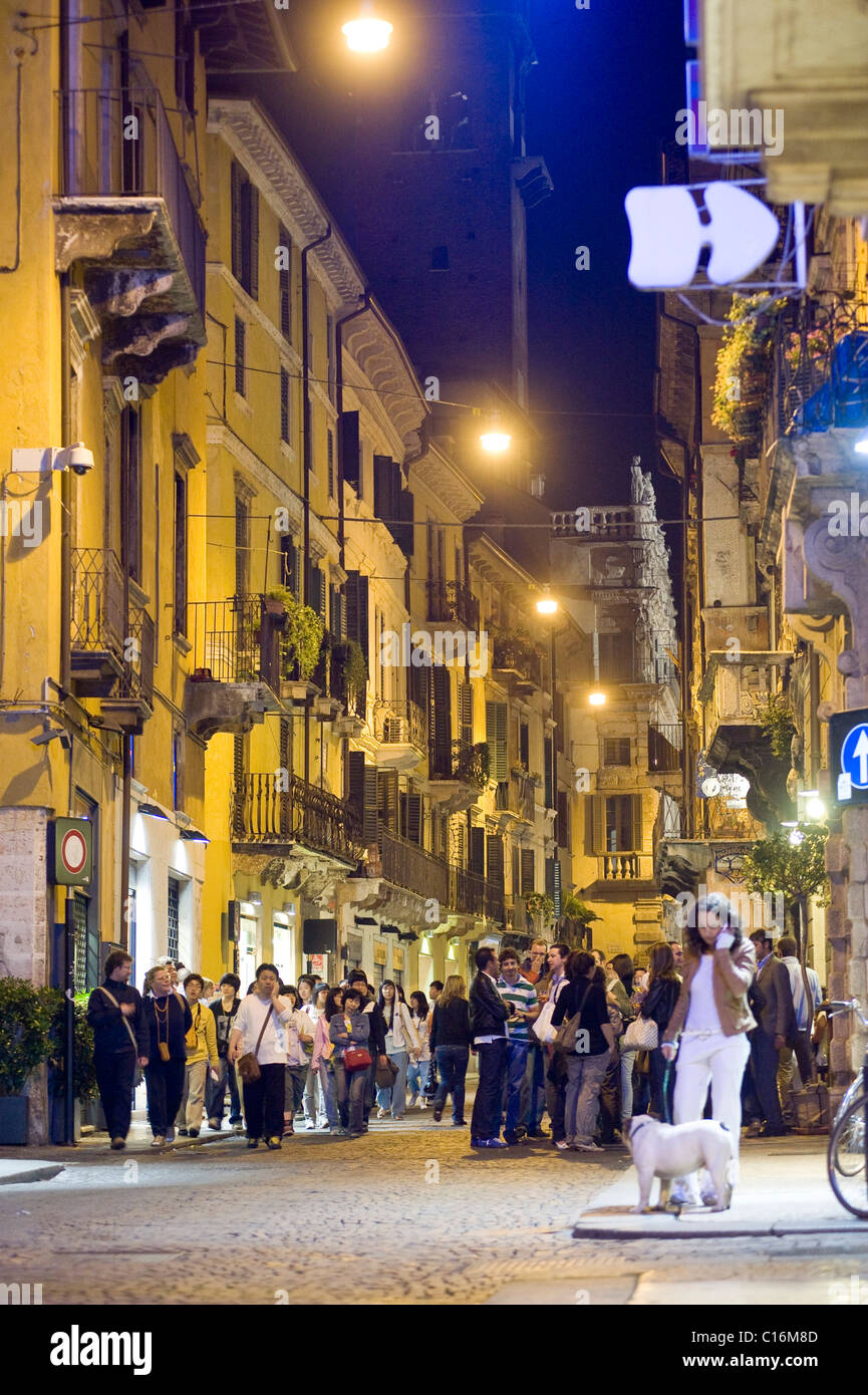 Youth gathered outside a pub in the historic centre of Verona, Italy, Europe - Stock Image