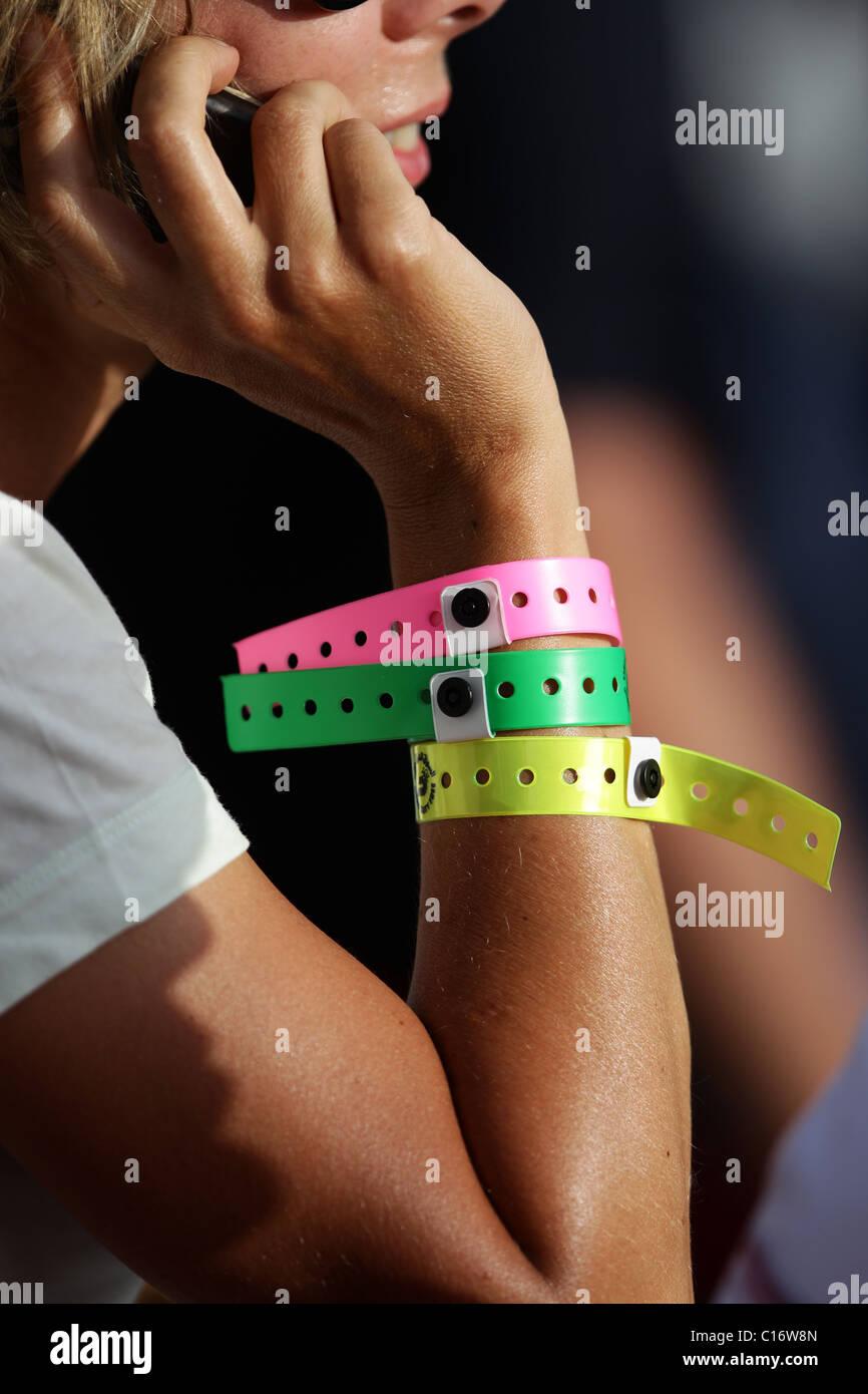 Woman wearing three VIP armbands - Stock Image