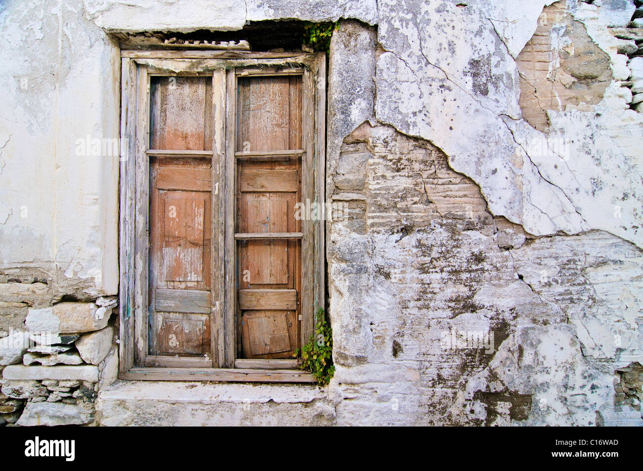 Old wooden window with weathered masonry in Naxos, Cyclades, Greece, Europe - Stock Image