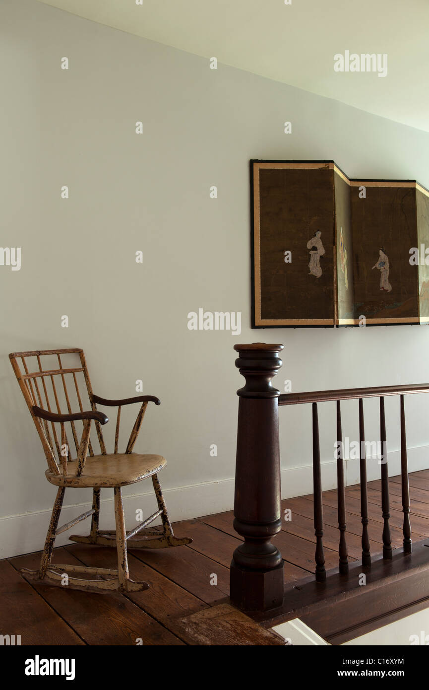 Rocking chair and Oriental folding screen on landing in 1830s Hudson Valley farmhouse, New York State - Stock Image