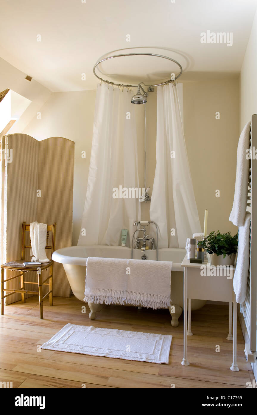 Freestanding Roll Top Bath With Circular Shower Curtain In Bathroom Folding Screen And Wooden Flooring