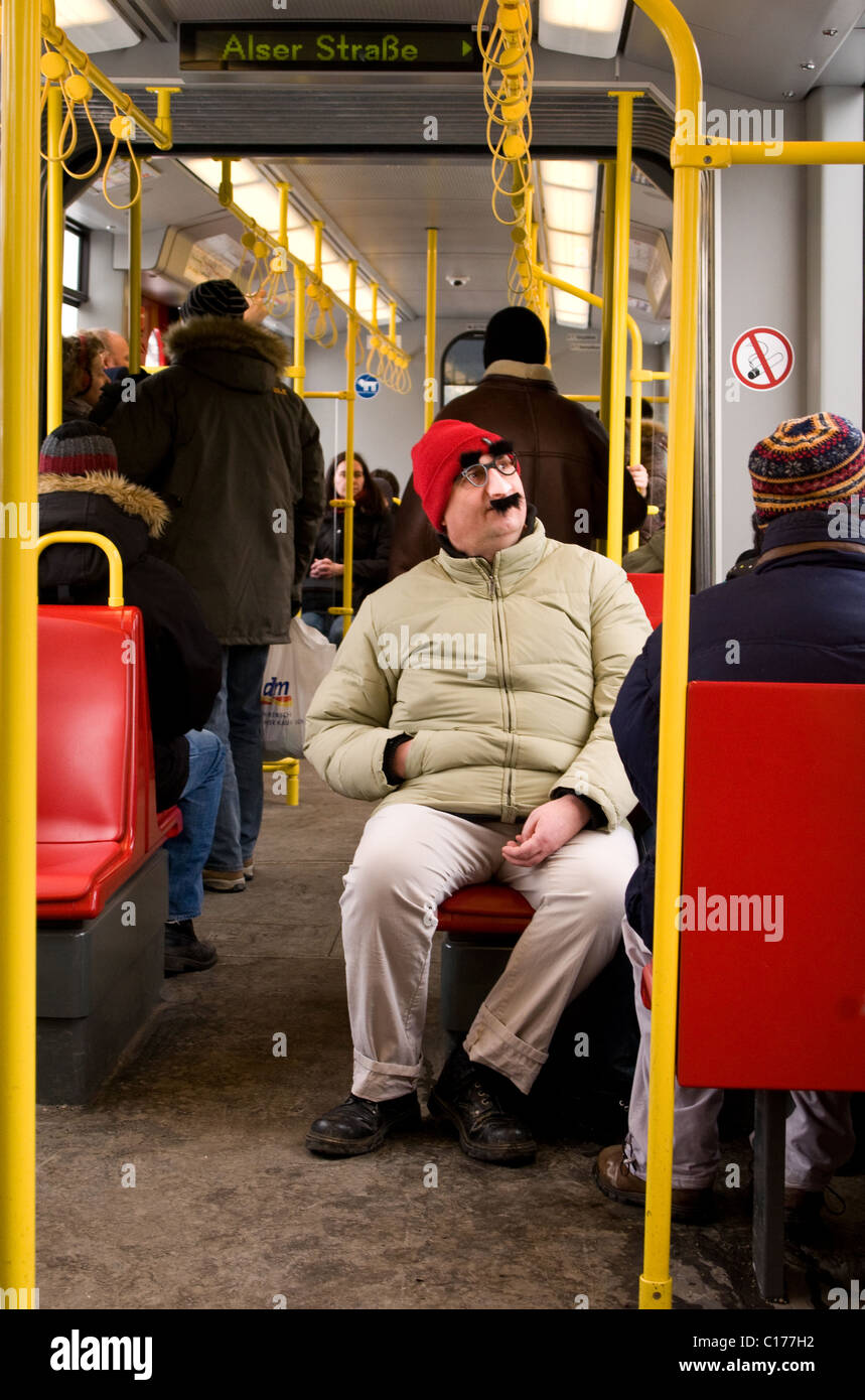 Passenger sits on the subway in a red hat and disguise kit. - Stock Image