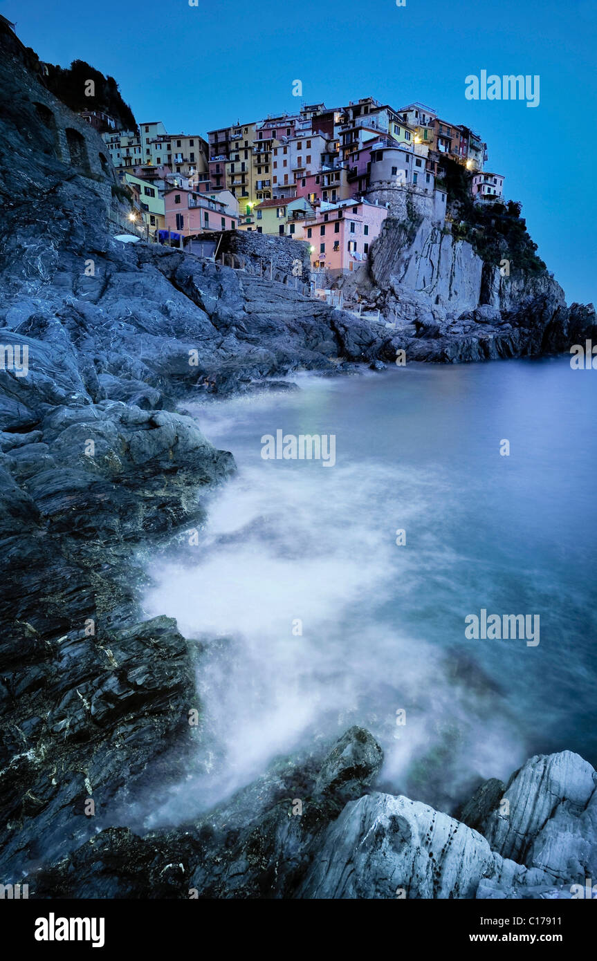 Waves breaking by the village of Manarola in evening light on the rugged steep coast in Liguria, Cinque Terre Stock Photo