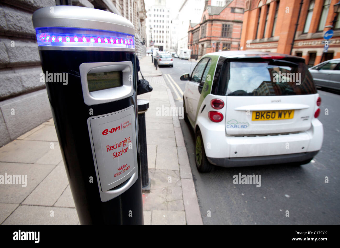 Electric Smart car and charging pint in the centre of Birmingham, England, UK - Stock Image