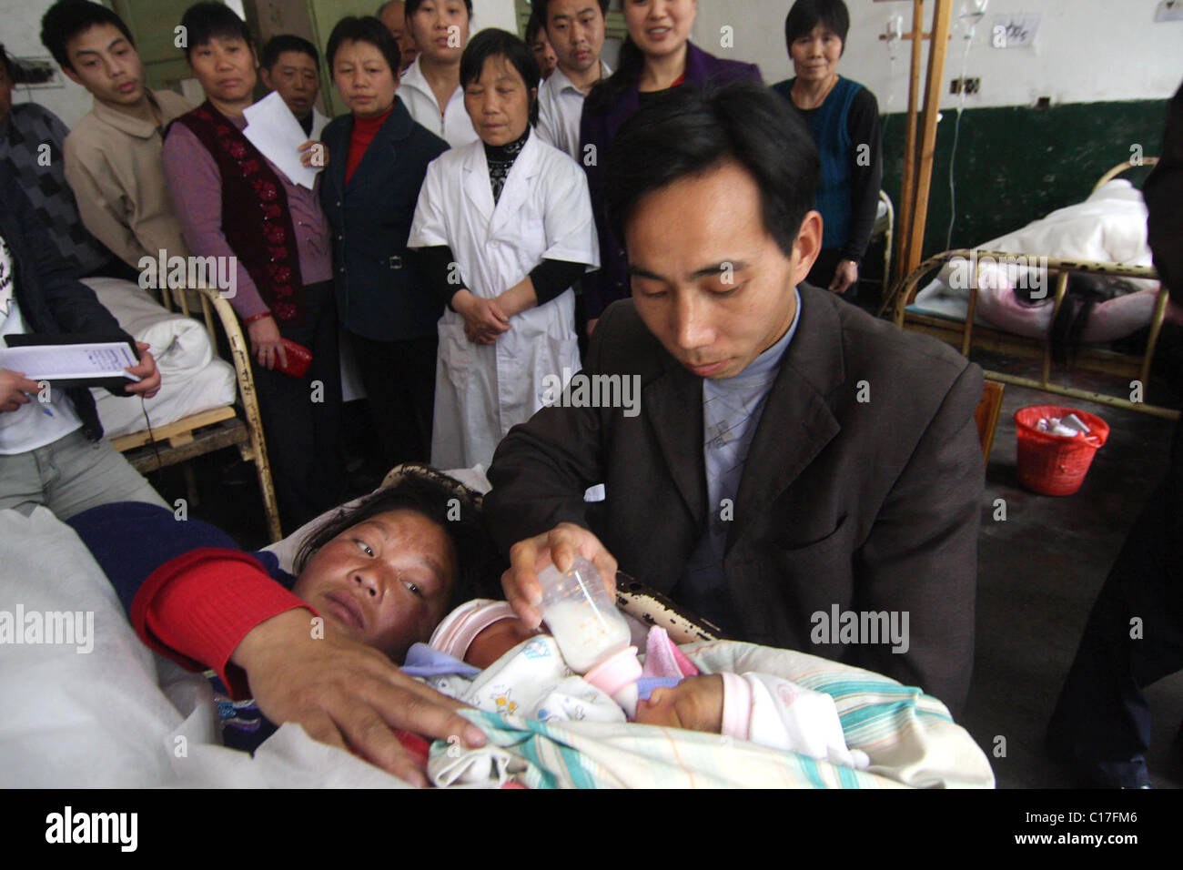 SURGEONS TO SEPARATE CONJOINED TWINS Two conjoined twins are tenderly fed by their loving parents just days before - Stock Image