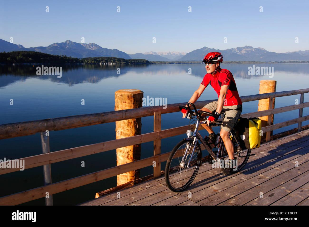 Bicyclist at Dampfersteg in Chieming, Chiemsee, lake, Chiemgau, Bavaria, Germany, Europe - Stock Image