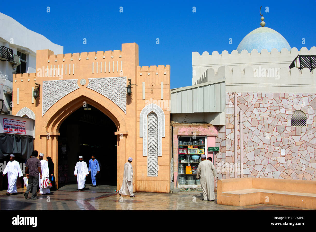 Local residents dressed in traditional clothes at the entrance gate to Souq Muttrah markets, Muscat, Oman, the Near - Stock Image