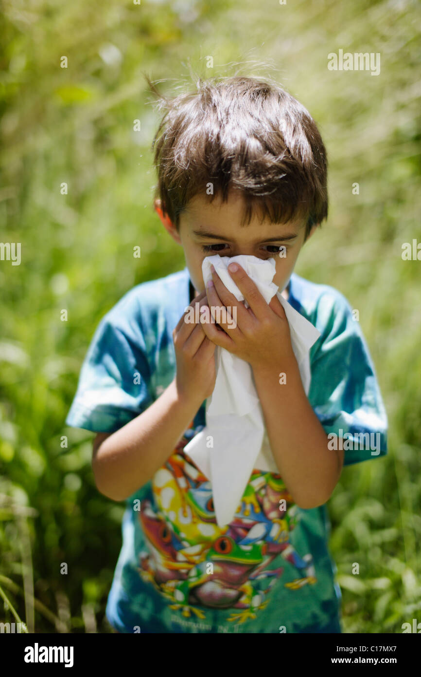 Six year old boy sneezing into tissue in garden - Stock Image