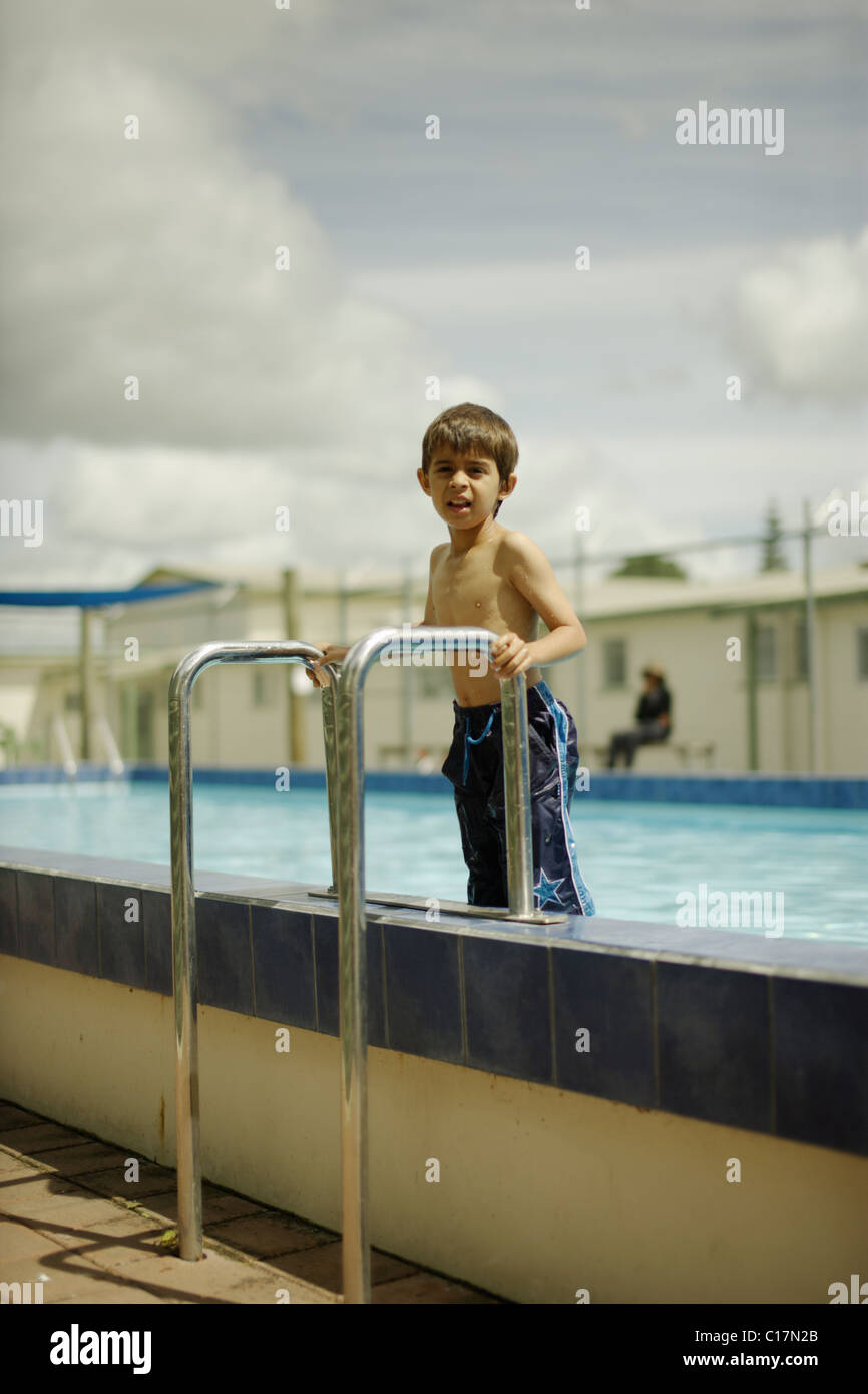 Six year old boy stands on steps as he gets out of the pool. Stock Photo