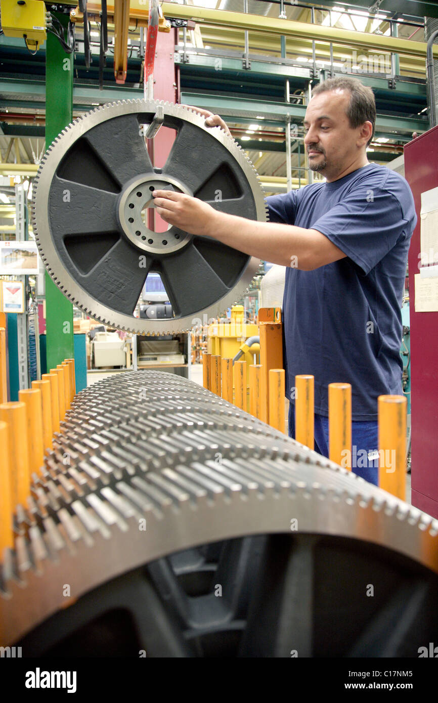 An employee of the Heidelberger Druckmaschinen AG preparing a gear for the processing in the manufacture of offset - Stock Image