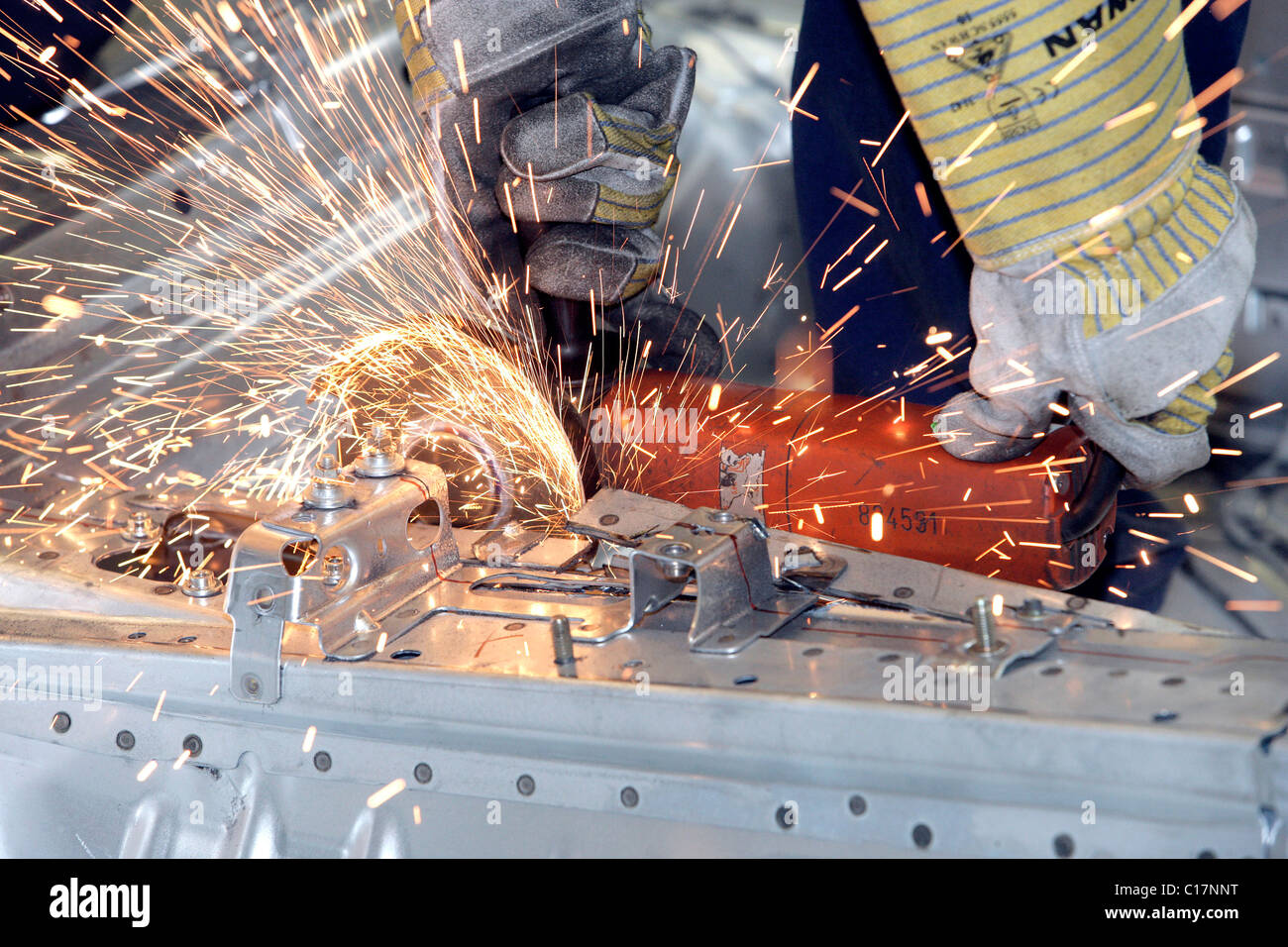 A trainee as Fertigungsmechaniker or assembly technician cutting metal with an angle grinder on the chassis of a - Stock Image