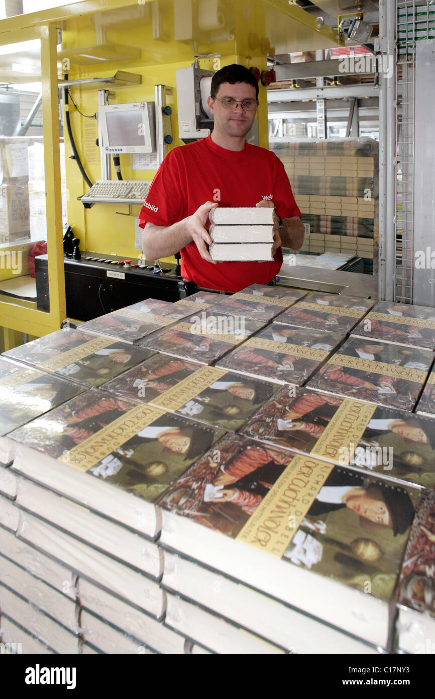 An employee of the Weltbild Publishing Group in the logistics centre taking a selection of books in a selective - Stock Image