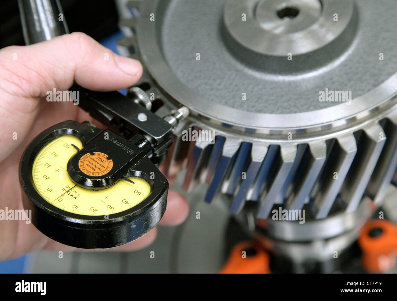 An employee of the Heidelberger Druckmaschinen AG checking the axial and radial runout of a gear with a dial gauge, - Stock Image