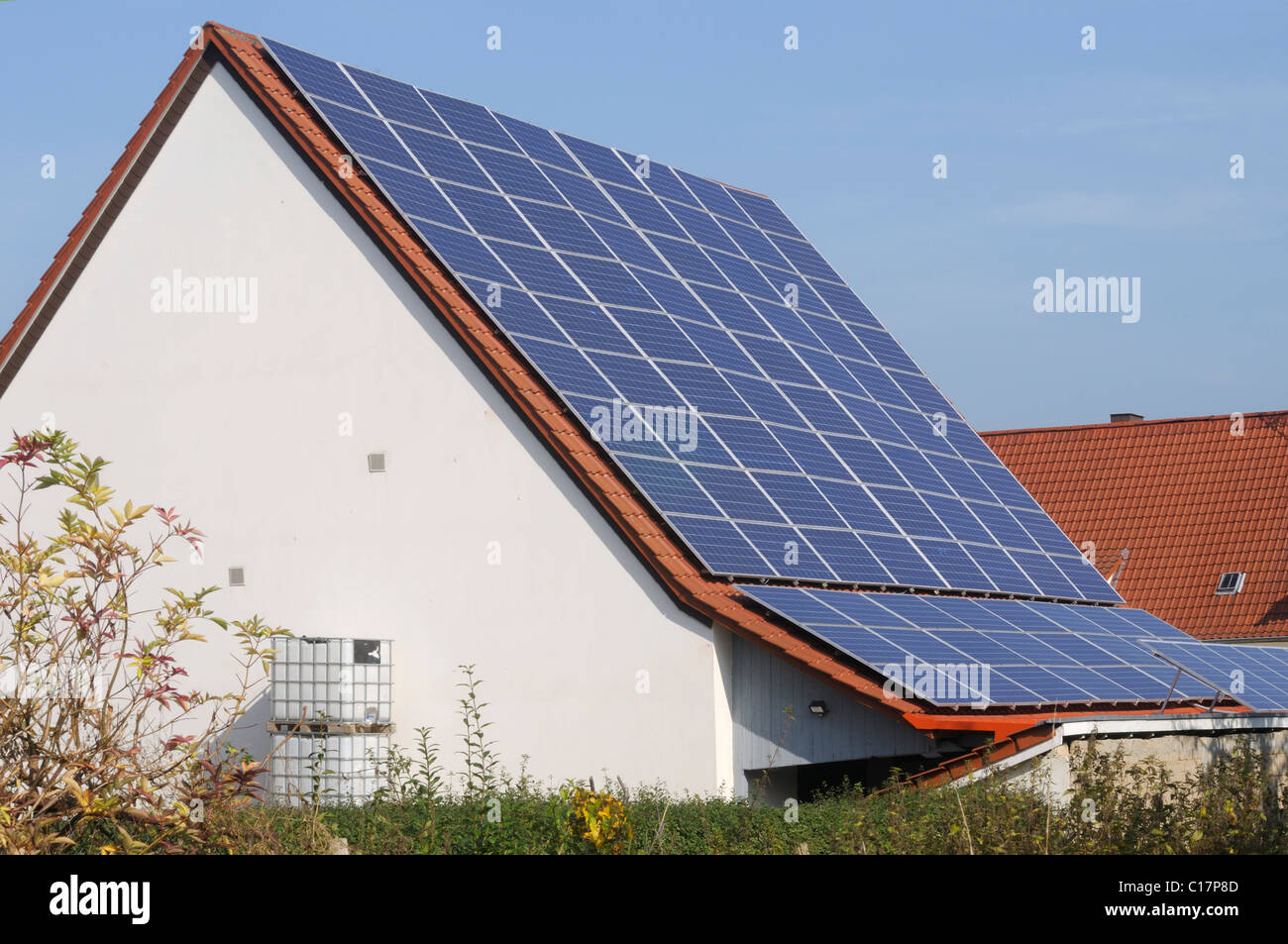Large roof with with solar collectors in a village - Stock Image