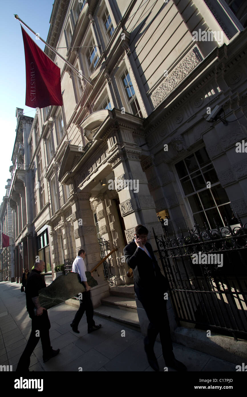 Christies auction house London porters carrying in artwork through front entrance - Stock Image