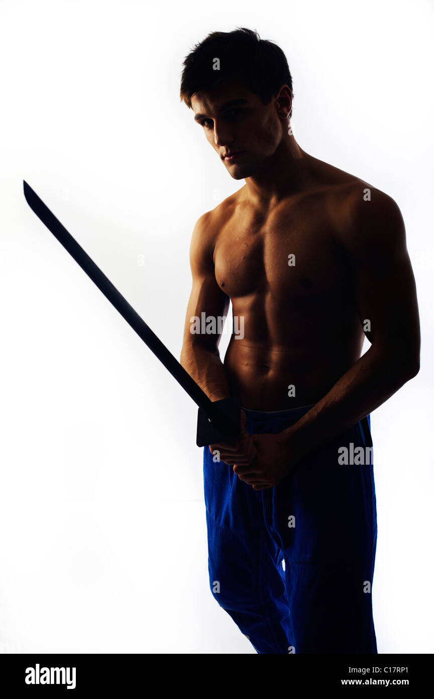 Young fighter with bare upper body holding a wooden sword, backlight - Stock Image