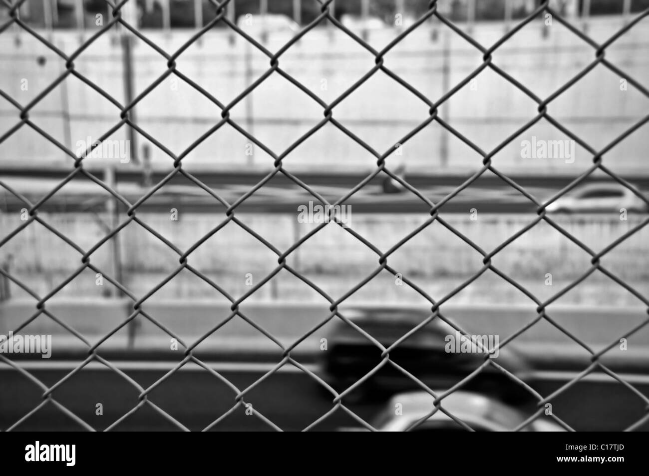 Speeding blurred cars on the motorway and wire mesh fence. Black and ...