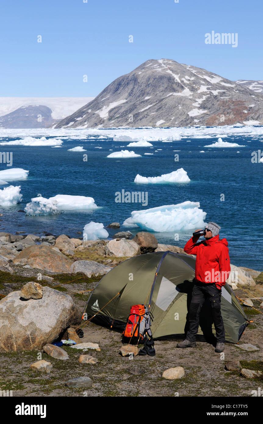Trekker, tent, camping in the Johan-Petersen-Fjord, East-Greenland, Greenland - Stock Image