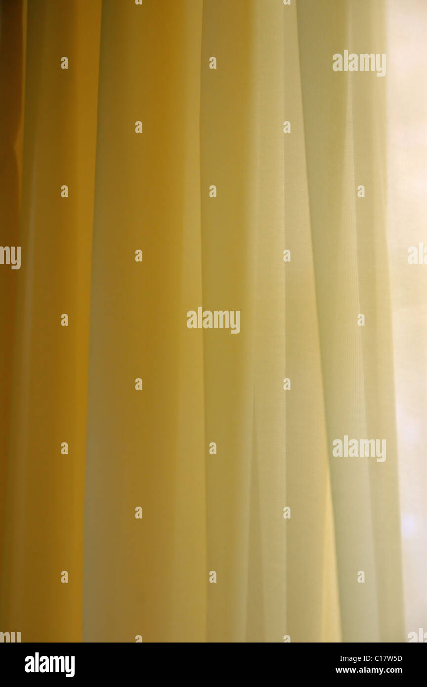 Transparent curtain background texture. Shades of yellow. - Stock Image