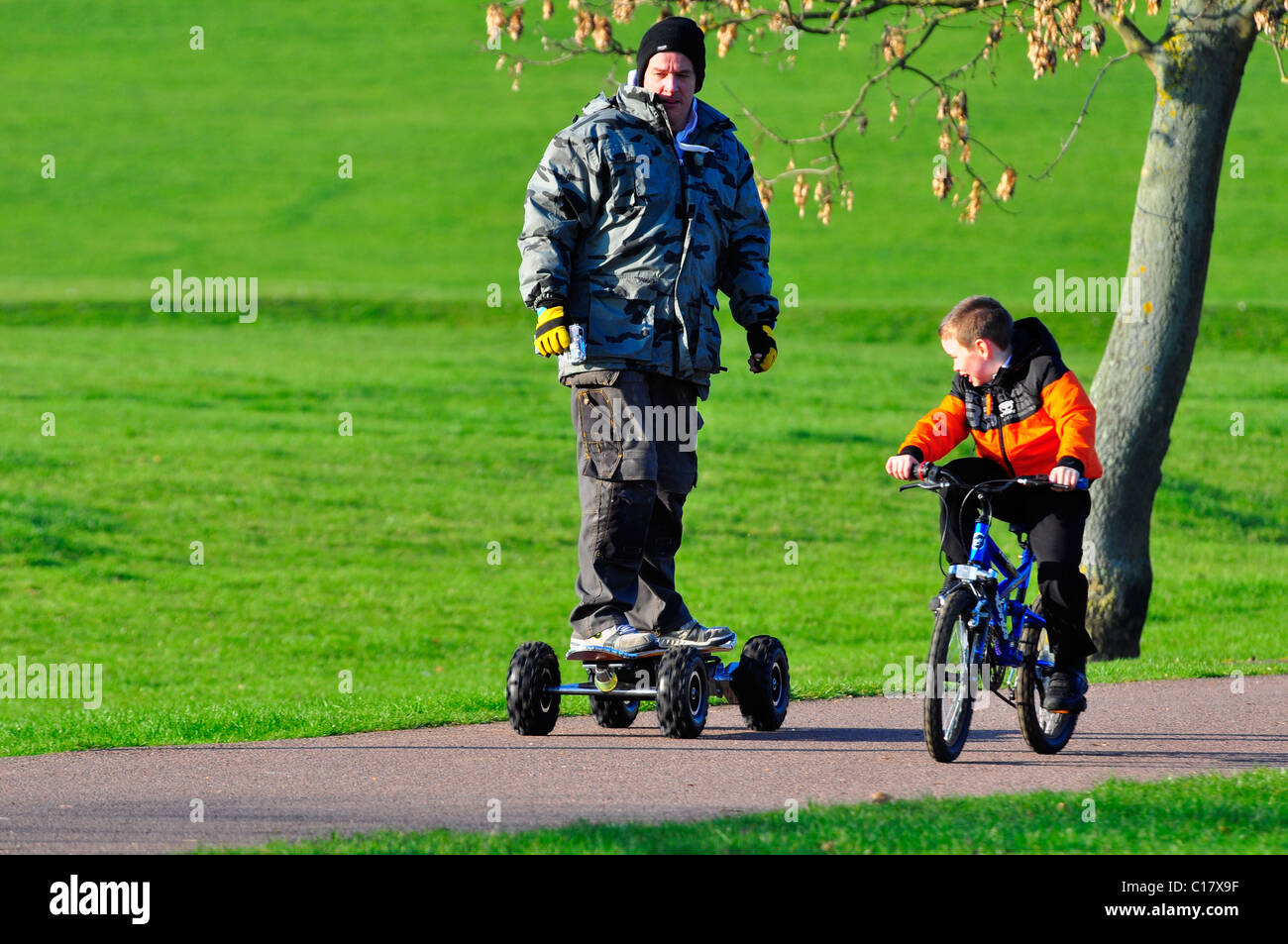 Man riding electric skate board with his son cycling along side - Stock Image