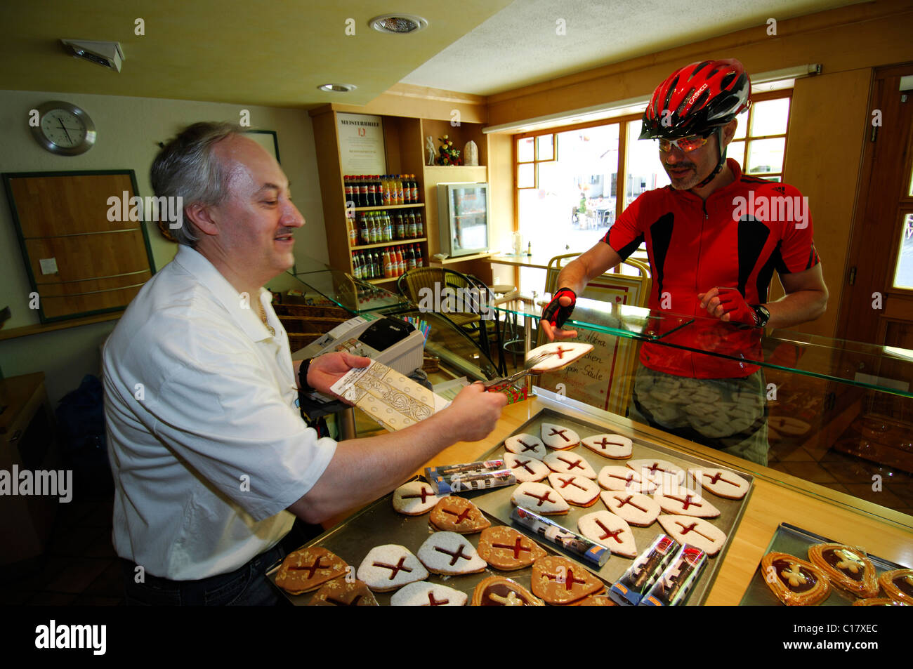 A cyclist purchasing pastries shaped like a mitre, in honor of Pope Benedict XVI, Marktl am Inn Stock Photo