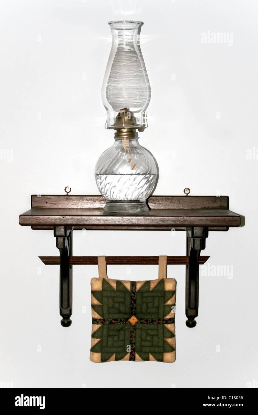 Amish old fashion kerosene lamp on the shelf with quilt wall decoration - Stock Image